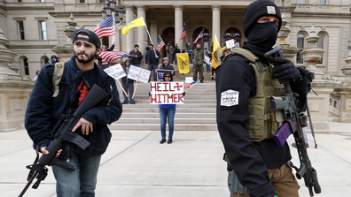 Protesters carry rifles near the steps of the Michigan State Capitol building in Lansing, Mich., Wednesday, April 15, 2020. (AP Photo/Paul Sancya)