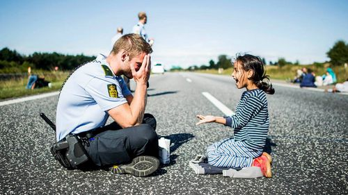 Syrian refugee girl finds joy in the antics of a Danish cop