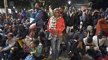 Migrants gather and wait before being evacuated from a makeshift migrant camp set up between the metro stations of Jaures and Stalingrad, in Paris, on September 16, 2016. (AFP)
