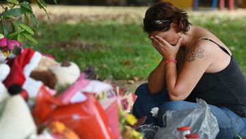 A shocked local sits at a makeshift shrine near the site of the incident. (9NEWS)