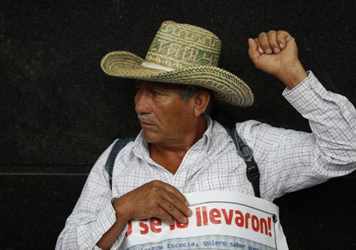 Margarito Guerrero, father of missing student Jhosivani Guerrero de la Cruz, raises his fist during a protest by relatives of the 43 missing teacher's college students outside the attorney general's office in Mexico City, 2019. While the families continue to call for justice, authorities have begun searching a new location in Guerrero state.