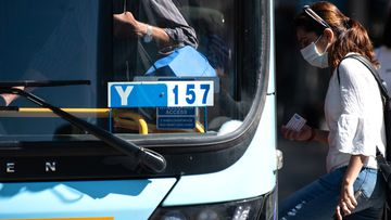 A woman wearing a protective face mask boards a bus in Sydney