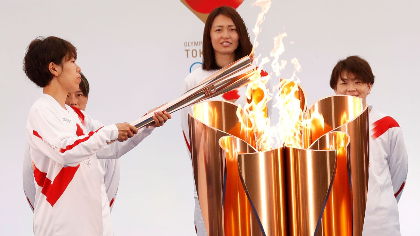 Japanese torchbearer Azusa Iwashimizu (C), a member of Japan women's national football team, arrives at a torch kiss point to pass on the flame. (Getty)
