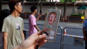 A resident holds up a phone cover depicting US President Donald Trump for a photo outside the United States Consulate in Chengdu in southwest China's Sichuan province