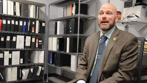 Detective Scott Marshall poses with some of the cold case files at the Battle Creek Creek Police Department.
