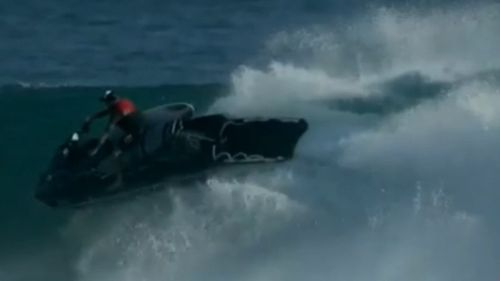 A jet ski rides out the huge waves.