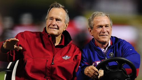 Former US Presidents George H.W. Bush (L) and his son George W. Bush (R) arriving on a cart to throw out the ceremonial first pitch before game four of the 2010 World Series at Rangers Ballpark in Arlington,Texas.