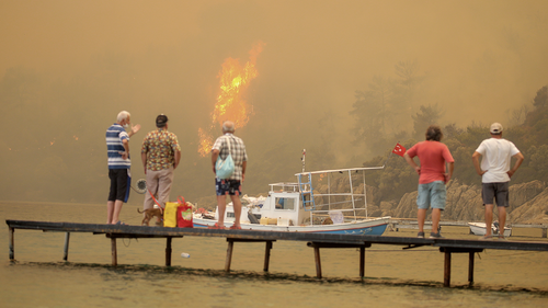 Tourists wait to be evacuated from smoke-engulfed Mazi area as wildfires rolled down the hill toward the seashore, in Bodrum, Mugla, Turkey, Sunday, Aug. 1, 2021