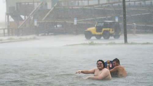 Two men play in hurricane floodwaters in Pensacola, Florida. Authorities warn not to do this.