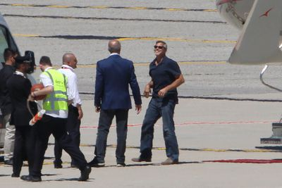The 56-year-old actor was in good spirits as he laughed with staff on the tarmac.