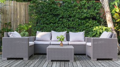 Large terrace patio with rattan garden furniture in the garden on wooden floor