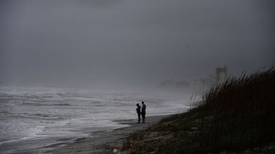 A beach in Florida turns dark as the storm approaches. (AP)