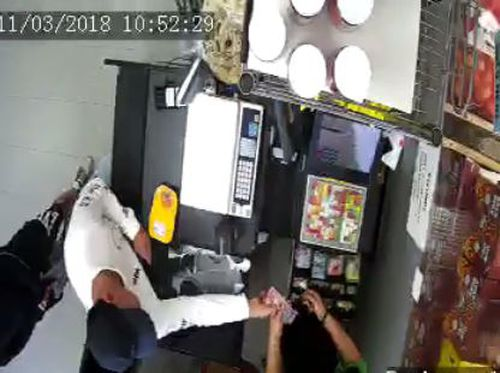 The thief starts by grabbing at the change initially handed to him by the cashier. (Supplied)
