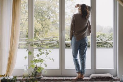 Woman standing at window at home