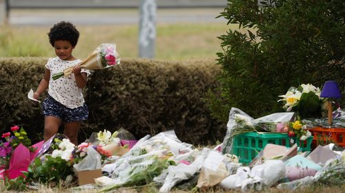 A young girl leaves flowers at the growing memorial for Ms Maasarwe in Bundoora.