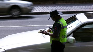 A parking inspector issues a ticket to a car parked on Macquarie Street in Sydney's CBD.