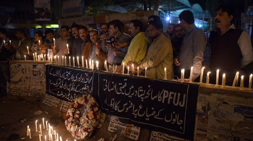 Pakistani journalists light candles for the victims of an attack by Taliban gunmen on a school in Peshawar. (Getty)