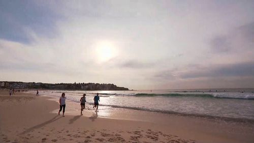 Beach walkers make the most of early temperatures before the mercury rises in Bondi.