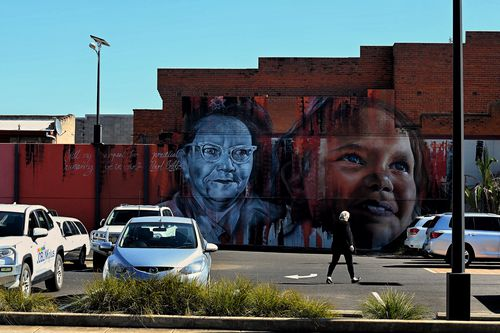 A woman walks across a car park in front of a mural on the side of a building on Talbragar Street in Dubbo, NSW. (Photo: Kate Geraghty)