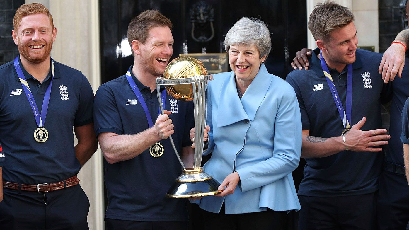 Britain's Prime Minister Theresa May smiles as she stands with England cricket captain Eoin Morgan, members of the team and the trophy