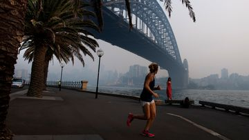 A jogger runs along the waterfront as smoke haze from bushfires sits over the harbour bridge