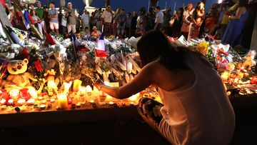 A woman and her child attend a vigil outside the French embassy