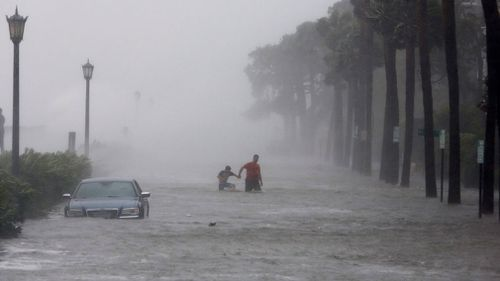 Pedestrians walk by a flooded car. (AP)