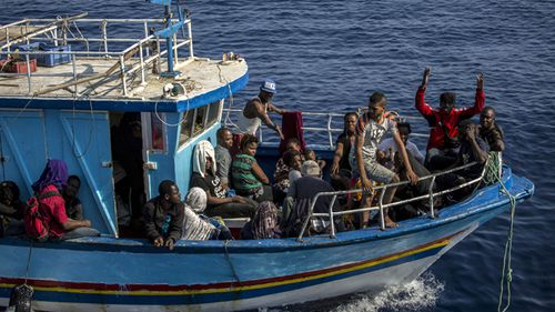 A migrant waves as others rest on their boat as it sails close to the Open Arms aid boat on Sunday June 30, 2019. A Spanish humanitarian group says its rescue ship spotted 40 dehydrated migrants at sea and their boat is now being escorted to the tiny Italian island of Lampedusa.