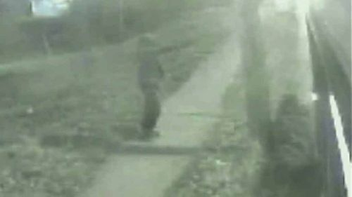 The gunman can be seen outside the bus, pulling out a gun. (Supplied)
