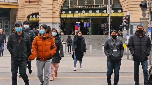 People in face masks outside Flinders Street Station in Melbourne.