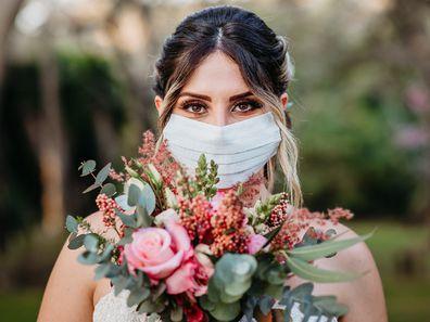 Bride holding flowers and wearing coronavirus mask.