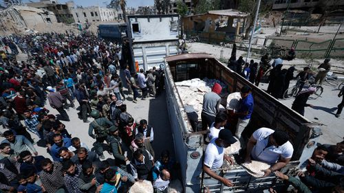 Syrian authorities distribute bread, vegetables and pasta to Douma residents. (AP/AAP)
