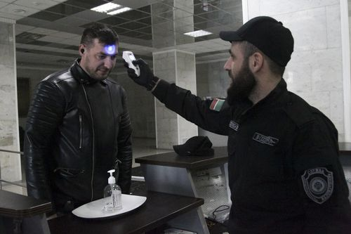 An security checks the body temperature of a man at an entrance of a building in Chechen provide capital Grozny, Russia.