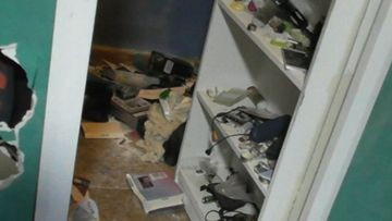 A man was allegedly found hiding behind this bookcase when police raided a house.