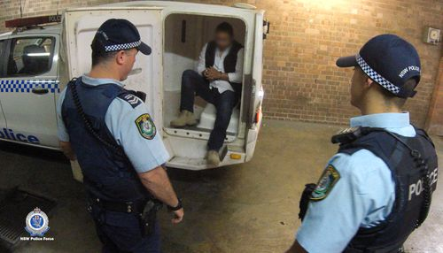NSW Police escort an arrested Guatemalan man out of a police vehicle, following his arrest.