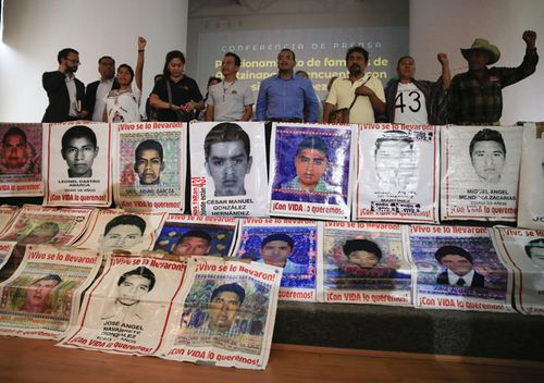 Parents of some of the 43 missing teacher's college students chant behind posters depicting their missing loved ones. Relatives complained that progress in the case has been too slow and some institutions are uncooperative.