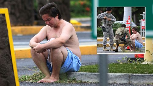 An unidentified male sits outside Pearl Harbour naval base after a fatal shooting.
