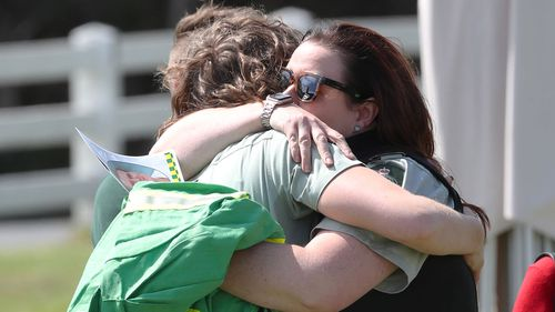 Loved ones embrace at the veteran firefighter's funeral.