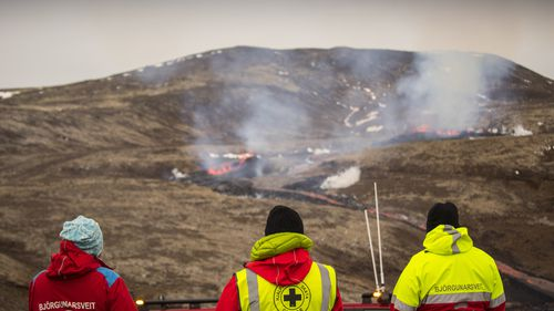 Members of the Search and Rescue Team, Bjorgunasveit look at a new fissure on a volcano on the Reykjanes Peninsula in southwestern Iceland.