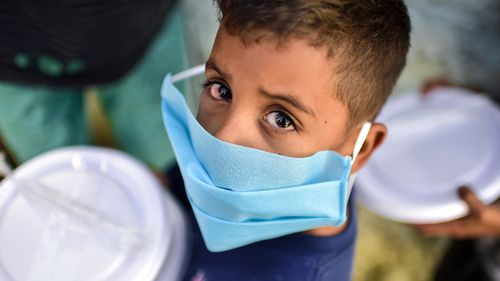 A young boy from a Brazilian favela lines up for a food donation. There has been a spike in deaths of children as the Gamma variant surges in the country.