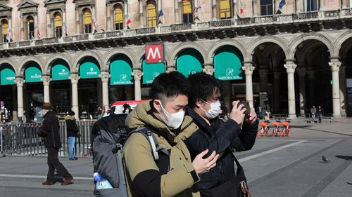 Two tourists are seen wearing a protective mask in the Duomo Square on February 28, 2020 in Milan, Italy