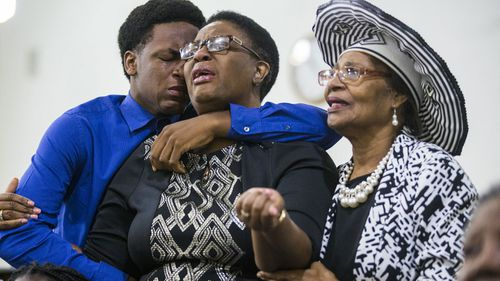 Grant Jean, 15, and his mother Allison Jean, who are the brother and mother of Botham Jean mourn with another churchgoer during a prayer service for Jean at the Dallas West Church of Christ