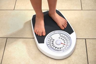 Child weighing themselves at home