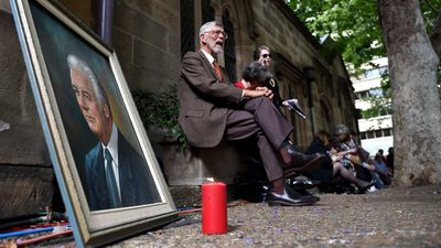 A portrait of Gough Whitlam with a candle sits across from the memorial service for the former Prime Minister outside Town Hall. (AAP)