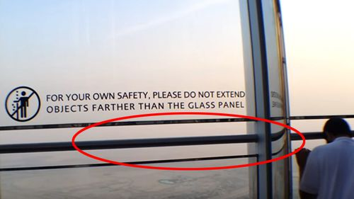 The viewing platform on the 148th floor of the Burj Khalifa, now with a bar in the gap and warning sign on the glass barrier. (YouTube)