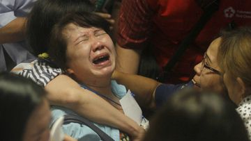 Relatives of passengers of the missing AirAsia flight QZ 8501 react to the news on television. (AAP)