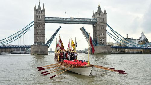 A Royal River Salute sails under Tower Bridge in London.