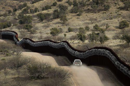 Seorang agen Pabean dan Pengawas Perbatasan berpatroli di sisi AS dari tembok perbatasan yang dilapisi kawat silet di sepanjang Meksiko timur Nogales, Arizona.