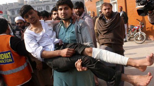 A Pakistani carries an injured victim of a massive Taliban attack on a school in the northwestern Pakistani city of Peshawar. (Getty Images)
