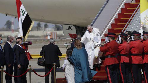 Paus Fransiskus berjalan menuruni tangga pesawat saat dia tiba di bandara internasional Baghdad, Irak, Jumat, 5 Maret 2021.